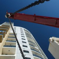 red crane in front of building