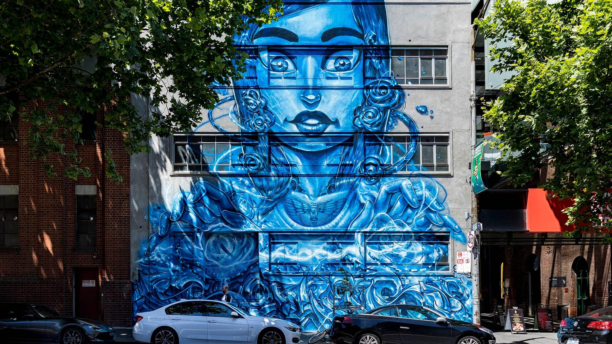 blue street art of woman on building exterior