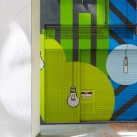 Colourful lightbulb art on building external wall