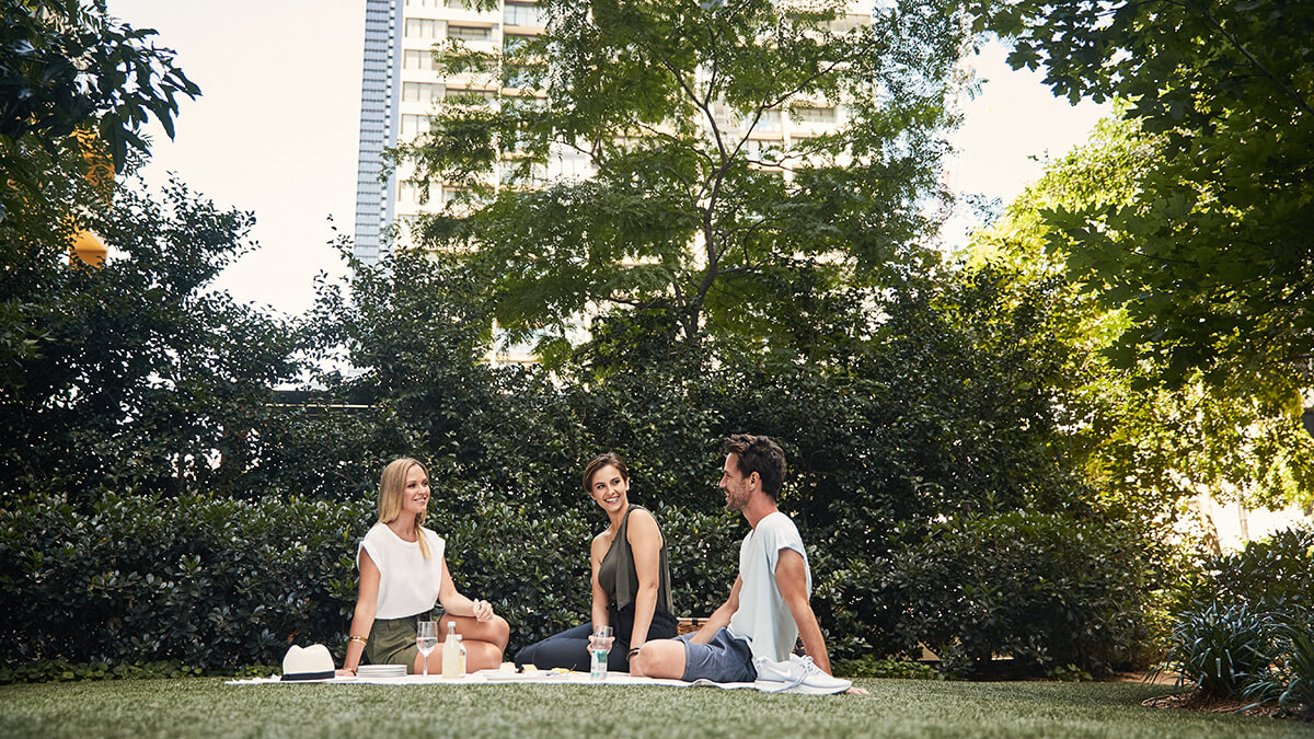 Two women and a man enjoy a picnic outdoors with wine in front of Upper West Side building
